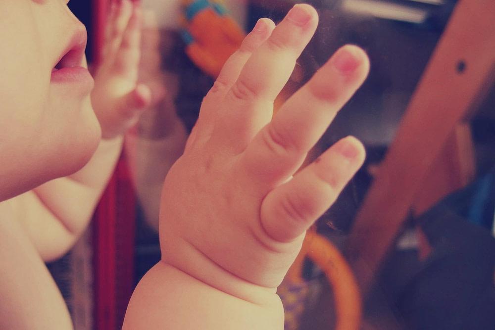 Das Baby schaut aus dem Fenster mit dem Hände. Die weite Welt ist zu sehen und ist neugierig auf die Kommunikation und die Welt der Menschen zu treffen. Sie können alles Wissenwertes über Hausgebärdensprachkurs sammeln.